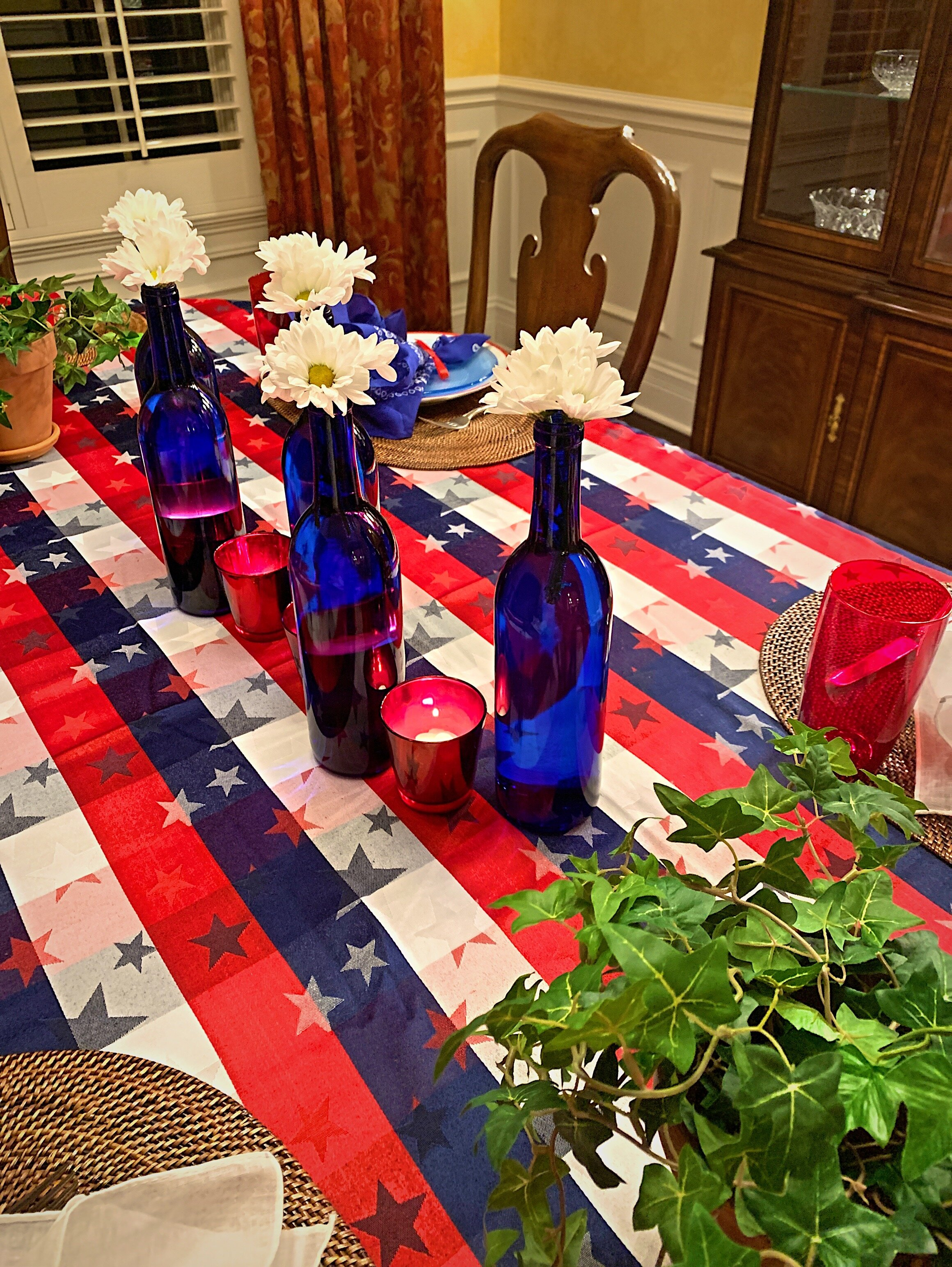 Blue glass bottles featured with white daisies, and red votives for a festive red, whit and blur centerpiece!