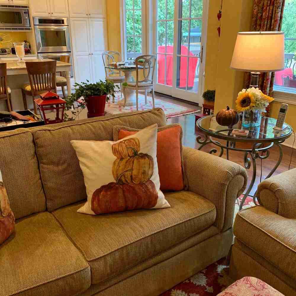 my fall home decor great room ideas with cute seasonal pillows and sunflower/hydrangeas on a side table.