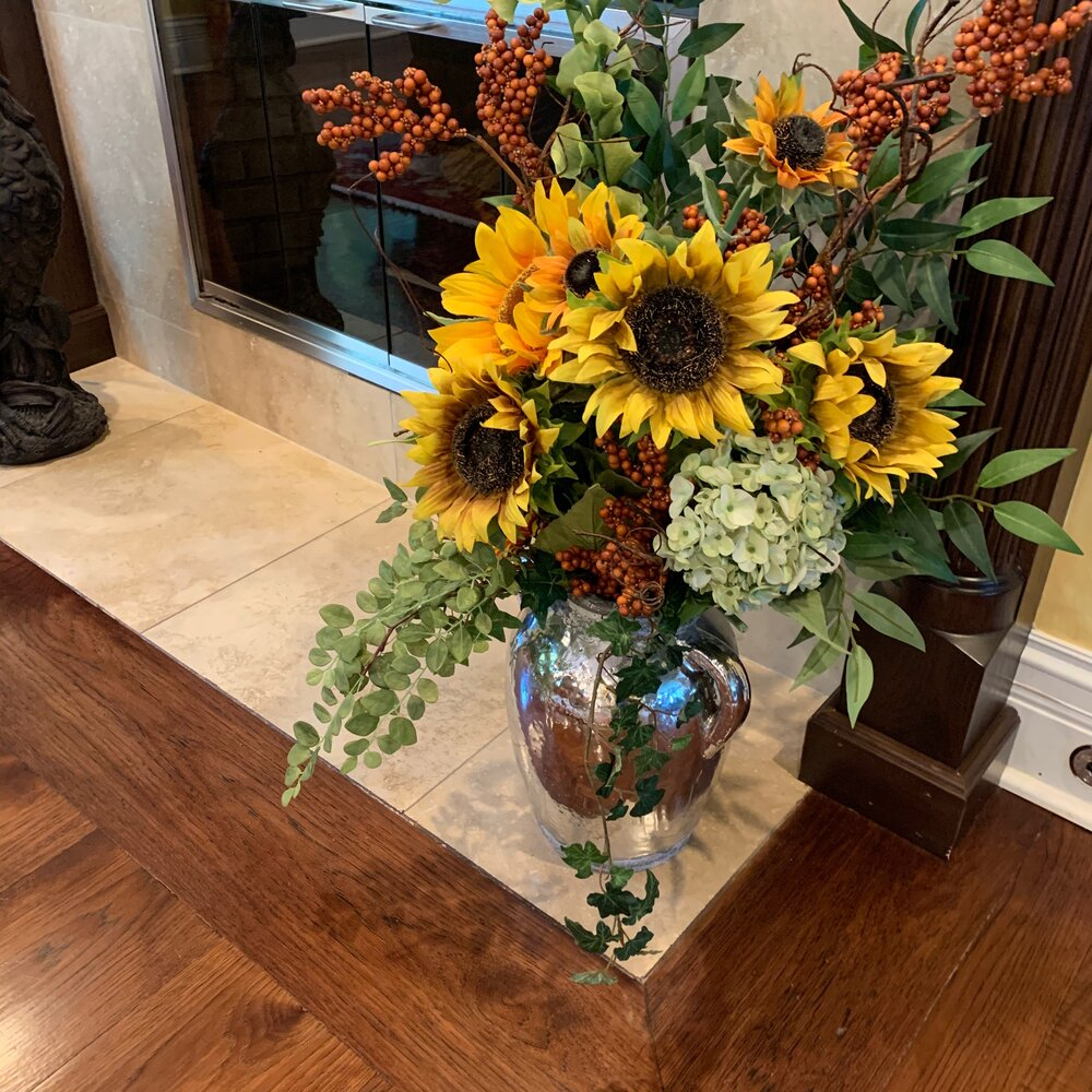 Introduction to my fall home decor. Here's a gorgeous silk arrangement with orange berries, sunflowers, bells of Ireland and hydrangeas in a silver urn.