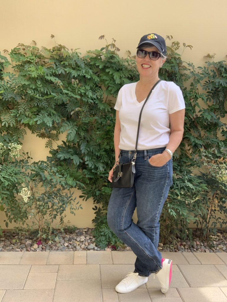 Jeans, white tee worn with a Blackhawks baseball cap, CUTE white sneakers, sunnies,  and a black crossbody bag