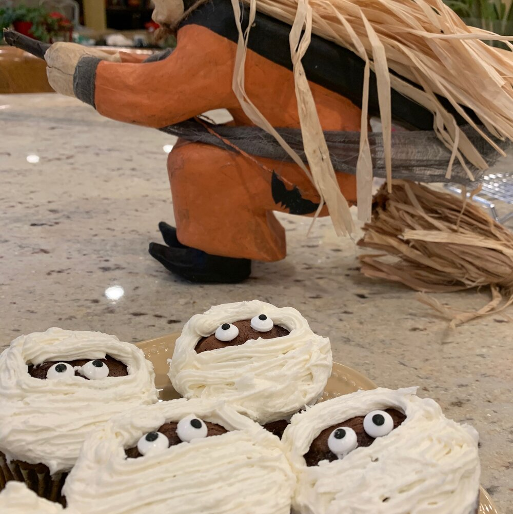 a photo of chocolate mummy cupcakes with white frosting and googly eyes peeking out through the bandages.  There's a witch behind the cupcakes.