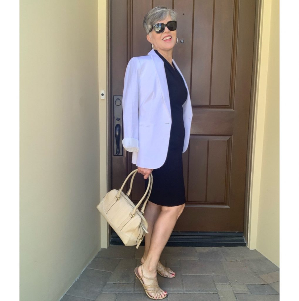 White linen blazer draped over my shoulders with a black sleeveless dress and a tan doctor's bag purse.