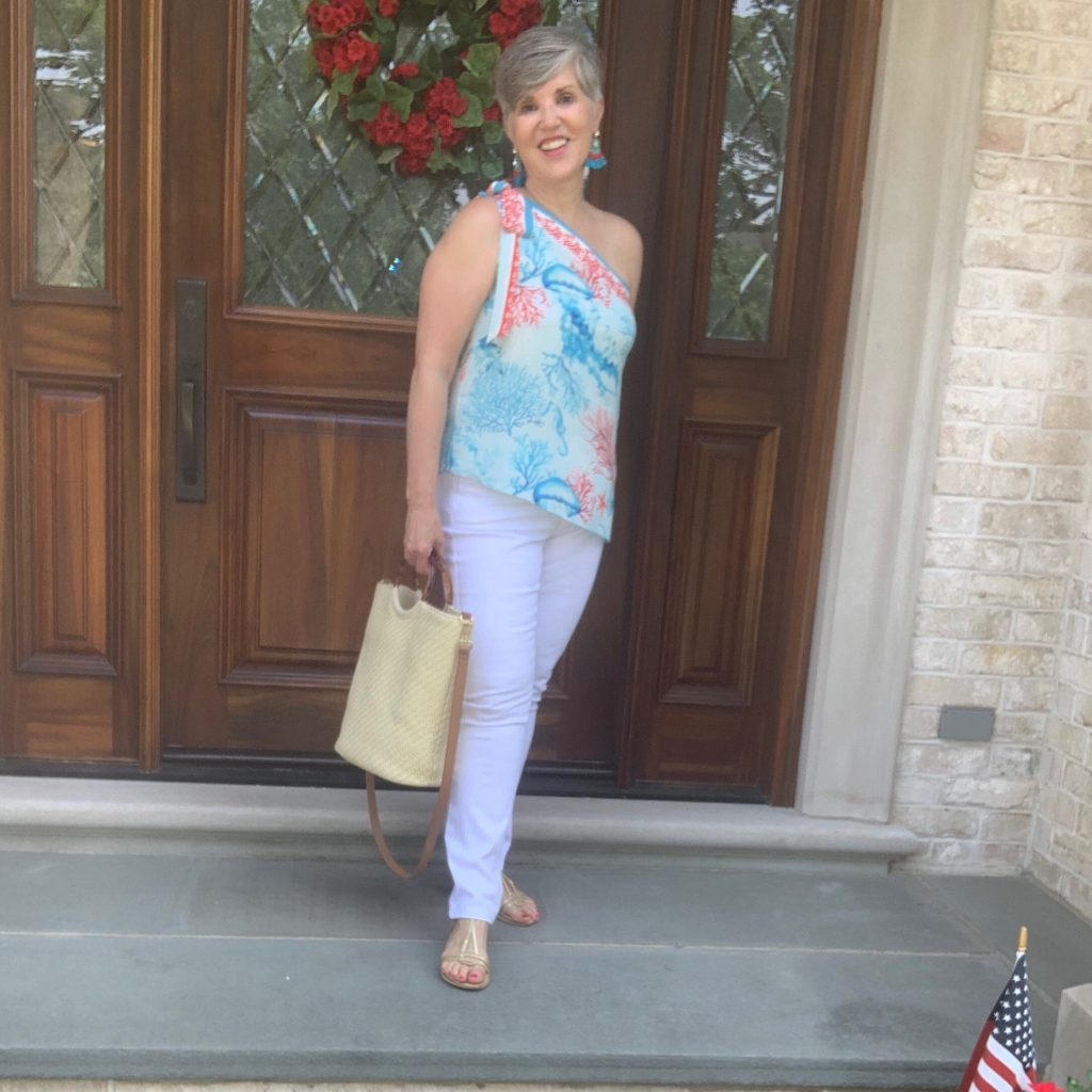 one shoulder top, white jeans, nude sandals, and a straw purse.