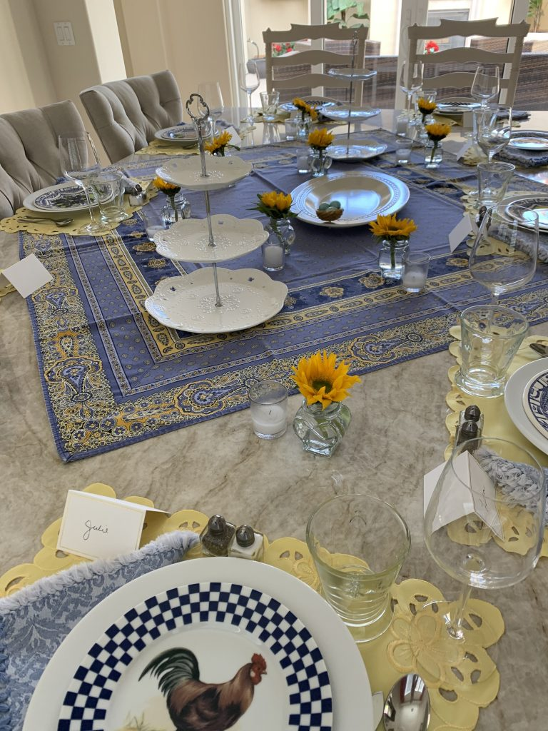 here is the beginning of my tablescape for the french-inspired tea party.  There are tiered cake stands, sunflowers in vases, little tea lights and French linens