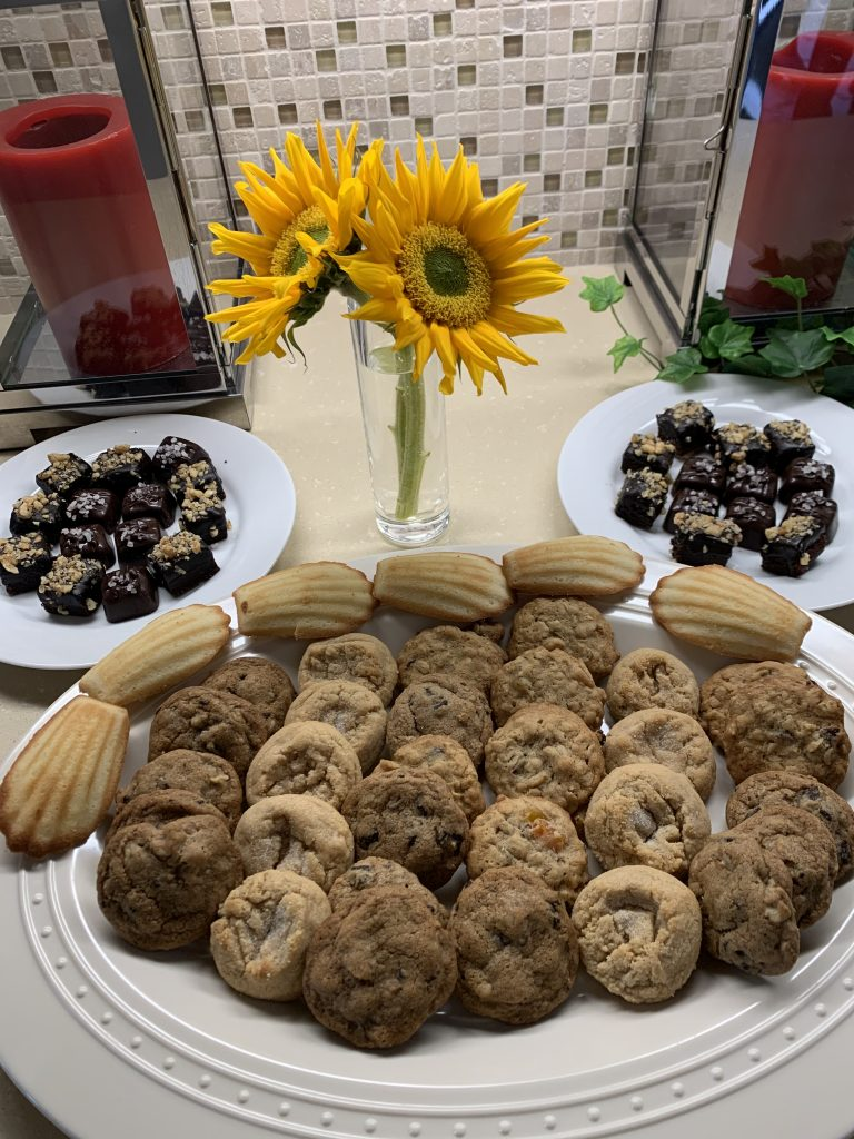 Sunflowers and sweets displayed on white platters next to red hurricane candles.