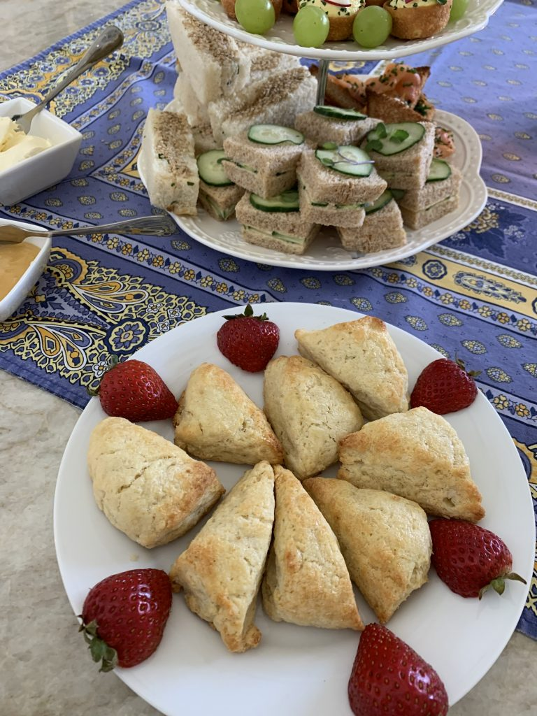 Gorgeous tea sandwiches, scones with strawberry garnishes, beautiful blue and yellow Provencal linens.