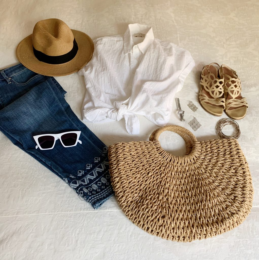 Embroidered jeans, white camp shirt, panama hat, white sunglasses, natural colored tote bag with nude sandals and silver jewelry.