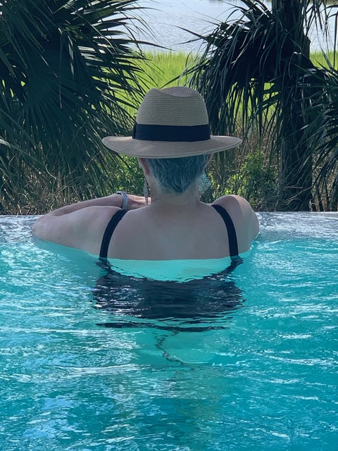 A photo of me from the back standing in a gorgeous infinity pool while wearing a black tank suit and a hat.