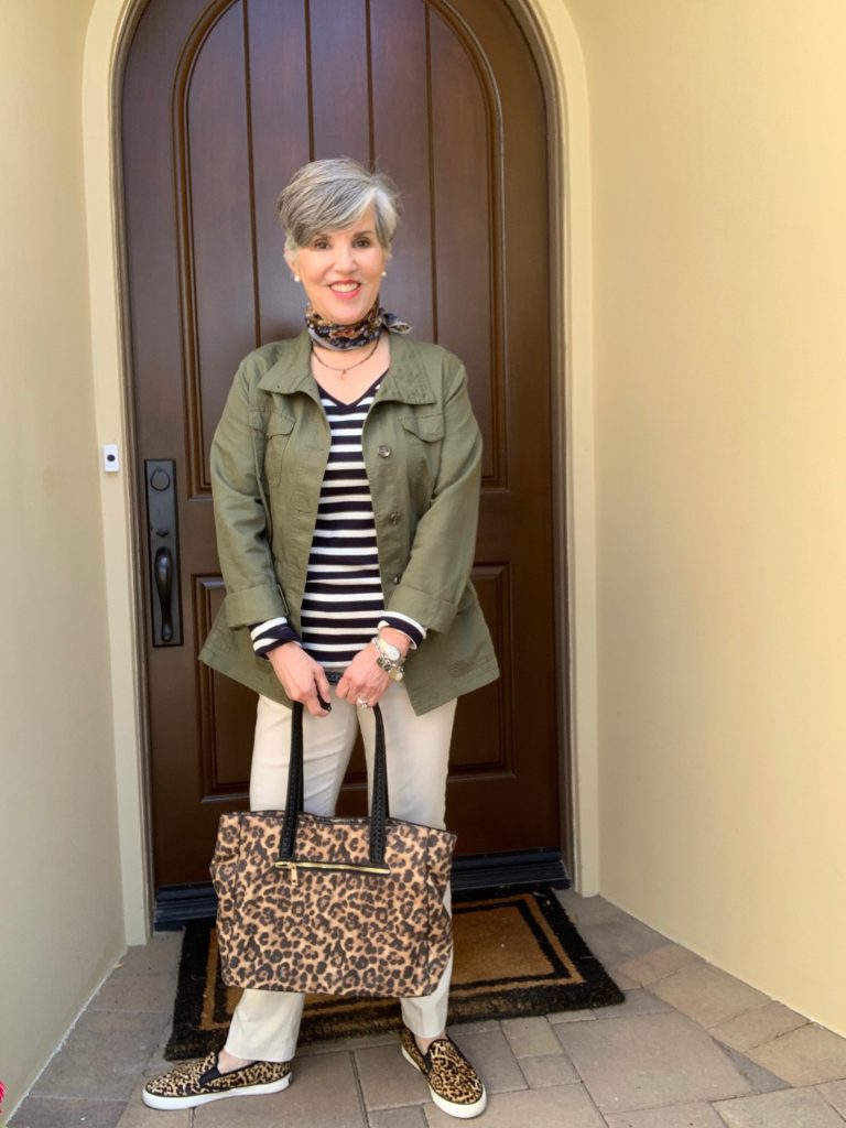 First outfit with tan chinos, leopard sneakers and tote, a striped tee and olive green utility jacket.