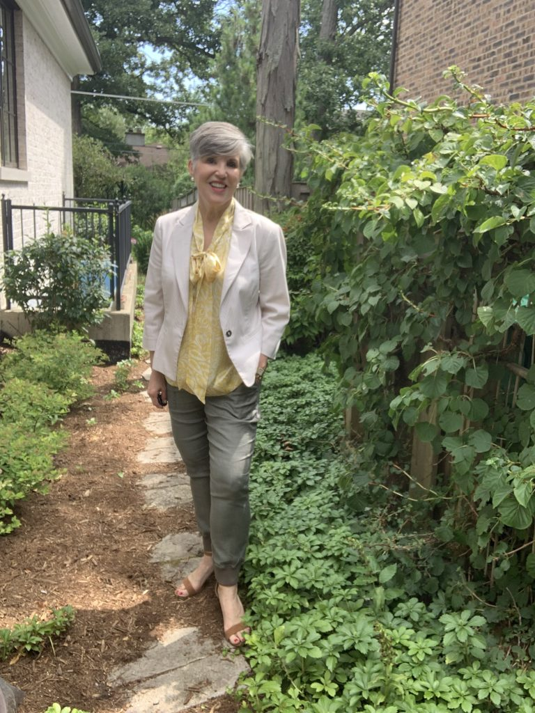Striped blazer worn over a yellow bow-neck top with olive pants in a green garden setting.