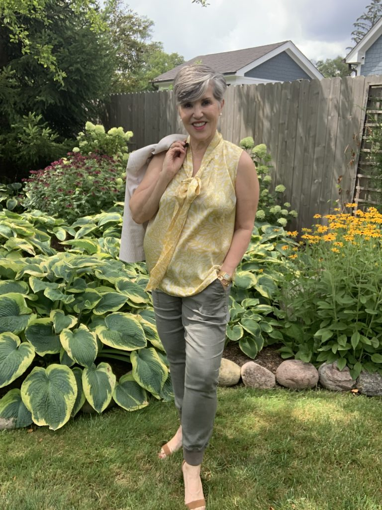 Sleeveless yellow print tie-neck blouse with a striped blazer over my shoulder.  Pearl earrings,  a gold watch and bangle, and olive jogger pants.  I'm standing in my late summer garden.